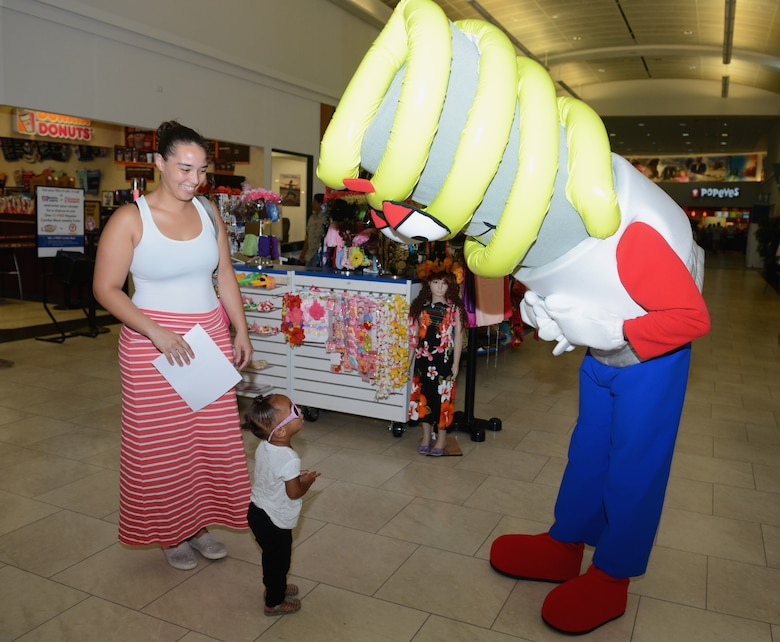 Energy Man, the energy awareness mascot, interacts with customers Oct. 21, 2015, at Andersen Air Force Base, Guam. Airmen with the 36th Civil Engineer Squadron informed Base Exchange patrons about the importance of energy conservation after the recent power incident that affected Guam's power grid. (U.S. Air Force photo by Airman 1st Class Arielle Vasquez/Released)