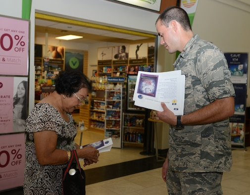 1st Lt. Joe Franklin, 36th Civil Engineer Squadron project programmer, right, shares energy awareness information with a Base Exchange customer Oct. 21, 2015, at Andersen Air Force Base, Guam. October marks Energy Awareness Month, reminding everyone that individual efforts can make a positive impact, especially after the recent power incident that affected Guam's power grid. (U.S. Air Force photo by Airman 1st Class Arielle Vasquez/Released)
