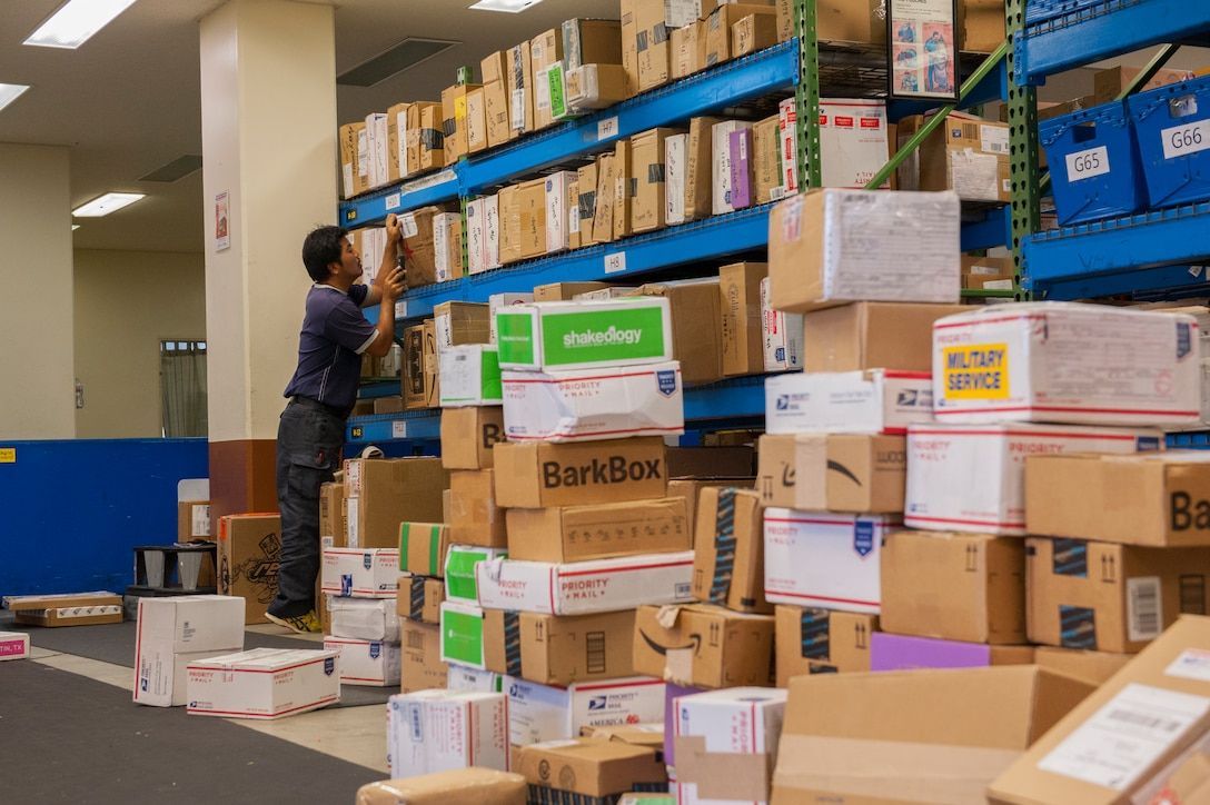 Kiyonobu Kuda, 18th Communications Squadron postal clerk, sorts and labels a large pile of packages at the Kadena Post Office Oct. 22, 2015, on Kadena Air Base, Japan. With the holidays approaching, the post office's hours are changing; starting Nov. 28 the pick-up window's hours will be Monday through Saturday from 9 a.m. until 7 p.m. (U.S. Air Force photo by Airman Zackary A. Henry)