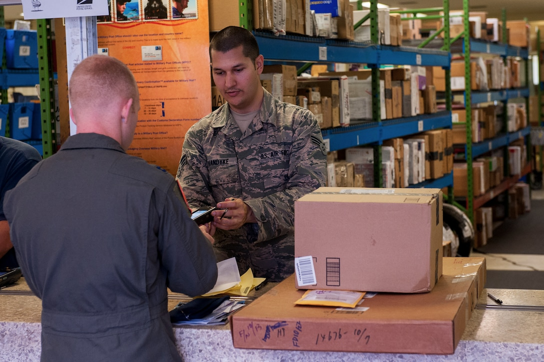 U.S. Air Force Senior Airman Adam Vandyke, 18th Communications Squadron postal clerk, assists Capt. Alex Khutoryan, 961st Airborne Air Control Squadron deputy chief of weapons and tactics, with his parcel at the Kadena Post Office Oct. 22, 2015, on Kadena Air Base, Japan. As the holidays draw closer, customers are asked to check their mailboxes daily to ensure there is room for the influx of packages expected to arrive on island over the next few months. (U.S. Air Force photo by Airman Zackary A. Henry)