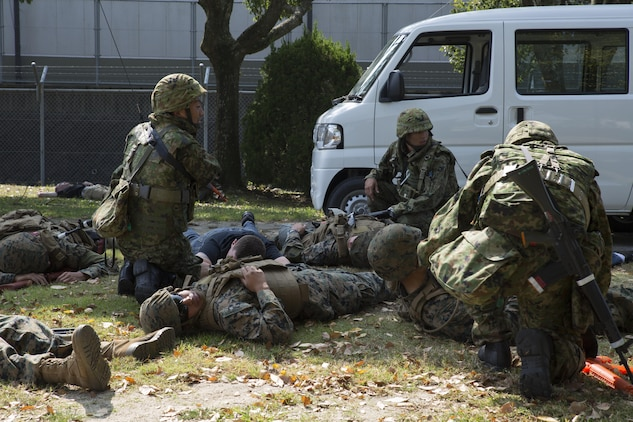 Marines and Japan Ground Self-Defense soldiers assess possible casualties in a simulated improvised explosive device explosion during Exercise Guard and Protect at Marine Corps Air Station Iwakuni, Japan, Oct. 20-23, 2015. Guard and Protect is a joint security force operation that enables readiness in case the station has to make a defense posture. The exercise tested the abilities of the Marines and Japanese soldiers to respond affectively in real world situations.