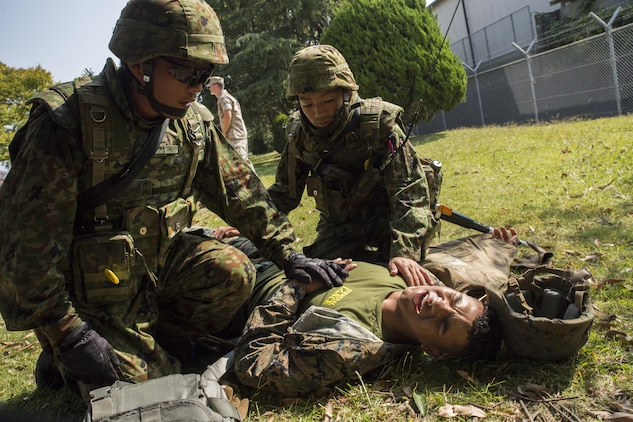 Japan Ground Self-Defense Force soldiers treat an injured Marine during a simulated improvised explosive device explosion during Exercise Guard and Protect at Marine Corps Air Station Iwakuni, Japan, Oct. 20-23, 2015. Exercise Guard and Protect is a joint security force operation that enables the station's readiness in case the station has to make a defense posture. During the exercise Marines and JGSDF soldiers had to overcome the language barriers in order to affectively accomplish the mission.