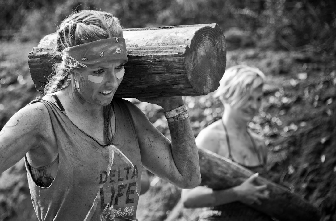 A competitor carries a wooden log through a mud pit during the Pensacola Mud Run Oct 24. Active duty and reserve service members from many local military bases came out to get dirty in the five-mile, 20-obstacle challenge.  (U.S. Air Force photo/Tech. Sgt. Sam King)