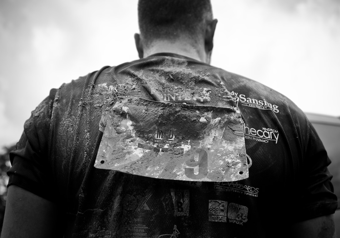 A competitor's shirt and bib are caked with mud after completing the Pensacola Mud Run Oct 24. Active duty and reserve service members from many local military bases came out to get dirty in the five-mile, 20-obstacle challenge.  (U.S. Air Force photo/Tech. Sgt. Sam King)