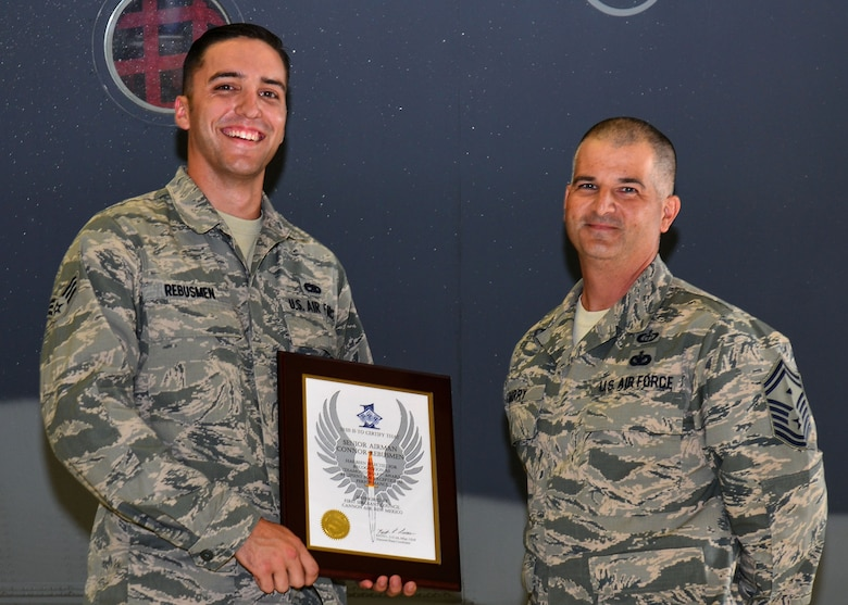 U.S. Air Force Senior Airman Connor Rebusmen, 27th Special Operations Aircraft Maintenance Squadron crew chief, stands with Senior Master Sgt. Bill Barry, 27th SOAMXS first sergeant, during his Diamond Sharp Award recognition Aug. 14, 2015, at Cannon Air Force Base, N.M. Rebusmen is an MC-130J crew chief assigned to the 9th Aircraft Maintenance Unit, who spends ample time setting the bar for community involvement within his squadron. (U.S. Air Force photo/Airman 1st Class Shelby Kay-Fantozzi)