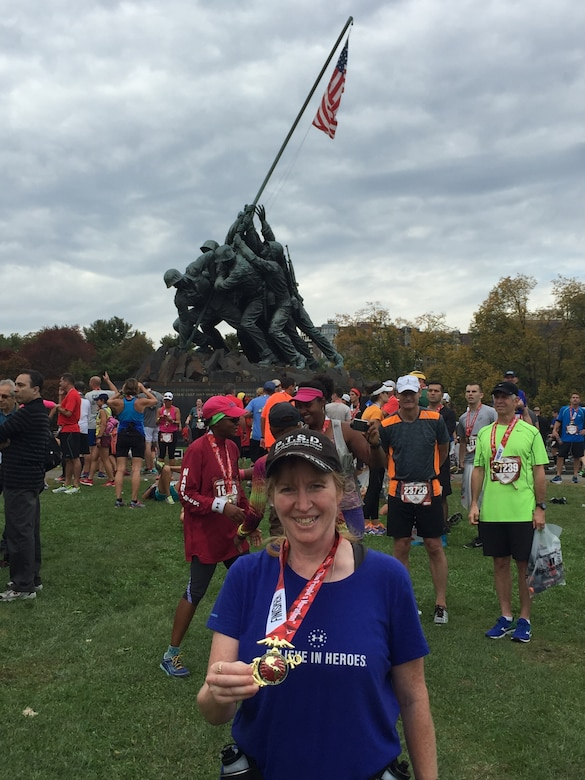 Shannon Collins with her medal in front of the Iwo Jima Memorial after completing the Marine Corps Marathon Oct. 25.