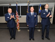 Oregon Air National Guard Combat Operations Group Commander Col. Mark Crosby, left, and Lt. Col. Matt Doggett, right, congratulate Maj. Joseph Lontai, center, after the formal exchange of colors during the Change of Command ceremony for the 123rd Weather Flight, Sept. 13, 2015, Portland Air National Guard Base, Ore. The Weather Flight Change of Command symbolized one of the last official formalities of the Combat Operations Group prior to the Oct. 1, 2015 realignment of the four units under the 142nd And 173rd Fighter Wings. (U.S. Air National Guard photo by Tech. Sgt. John Hughel, 142nd Fighter Wing Public Affairs/released)