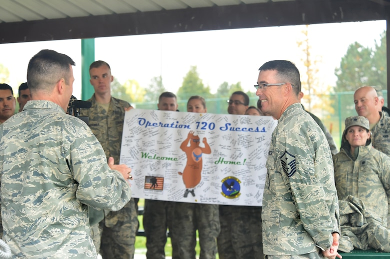 Team Buckley members celebrate Master Sgt. Troy Drasher's, 2nd Space Warning Squadron first sergeant, homecoming Oct. 22, 2015, on Buckley Air Force Base, Colo. Drasher received national attention after completing a run from Aurora, Colo. to Abilene, Texas, in order to raise money and awareness for wounded warriors. (U.S. Air Force photo by Airman 1st Class Luke W. Nowakowski/Released)