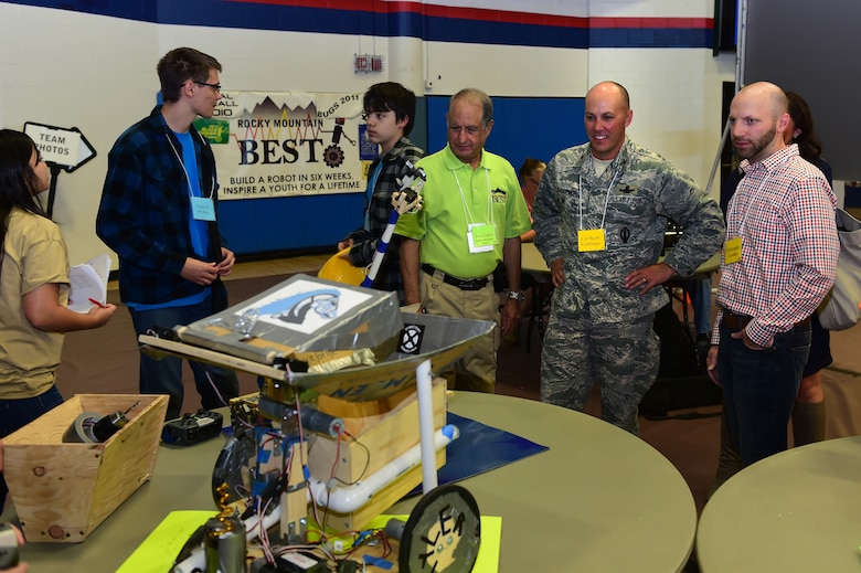 Col. Scott Romberger, 460th Space Wing vice commander, admires a remote-controlled robot alongside Jose Lopez, Rocky Mountain Boosting Engineering, Science and Technology Executive Director, Oct. 24, 2015, at the Auraria Campus Events Center, Denver. Romberger attended the Rocky Mountain BEST Robotics Competition in order to show support for a program that encourages Denver youth to participate and gain interest in projects involving engineering, science and technology. (U.S. Air Force photo by Airman 1st Class Luke W. Nowakowski/Released)