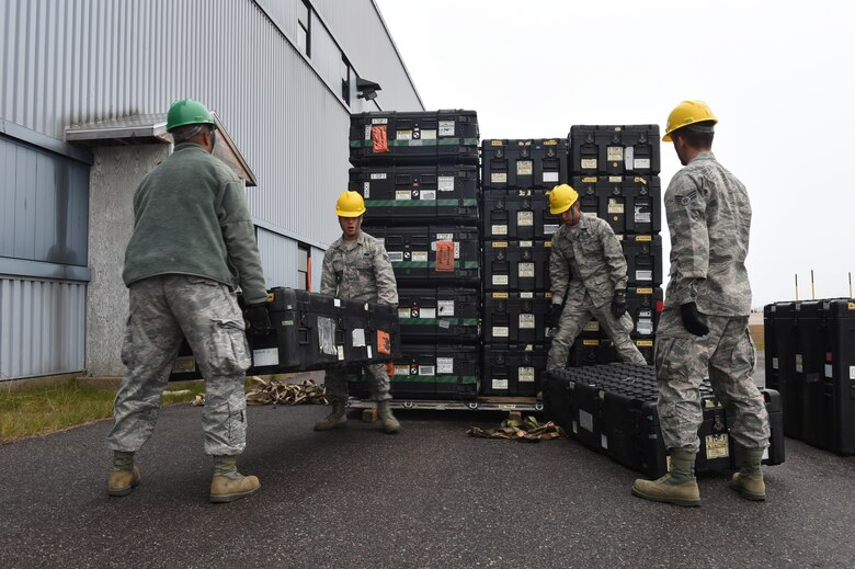 Airmen assigned to the 52nd Combat Communications Squadron move cases of communication equipment during Vigilant Shield 16 at 5 Wing Goose Bay, Canada, Oct. 10, 2015. From October 15-26, 2015 approximately 700 members from the Canadian Armed Forces, the United States Air Force, the United States Navy, and the United States Air National Guard are deploying to Iqualuit, Nunavut, and 5 Wing Goose Bay, Newfoundland and Labrador for Exercise Vigilant Shield 16. (U.S. Air Force photo by Senior Airman Jasmonet Jackson/ Released)
