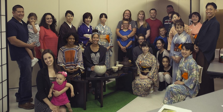 Station residents and instructors pose for a group photo during a tea ceremony with the Omotesenke Tea Ceremony Club hosted by the Cultural Adaptation Program at Marine Corps Air Station Iwakuni, Japan, Oct. 17, 2015. Programs like these help familiarize Americans with the culture of Japan, which they are now a part of.
