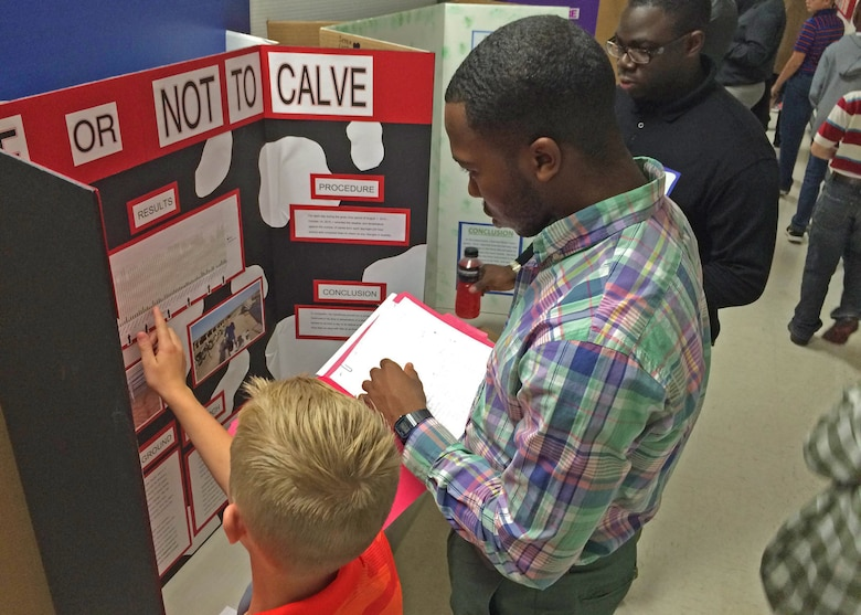 An Air Commando with the 27th Special Operations Wing judges a student's project during the local 2015 International Science and Engineering Fair, Oct. 23, 2015, in Clovis, N.M. Airmen had an opportunity to critique projects in a variety of categories, including microbiology, biomedical and health sciences, animal sciences, and cellular and molecular biology; all while meeting with students who presented their research in the name of science. (U.S. Air Force photo/Staff Sgt. Alexx Pons)