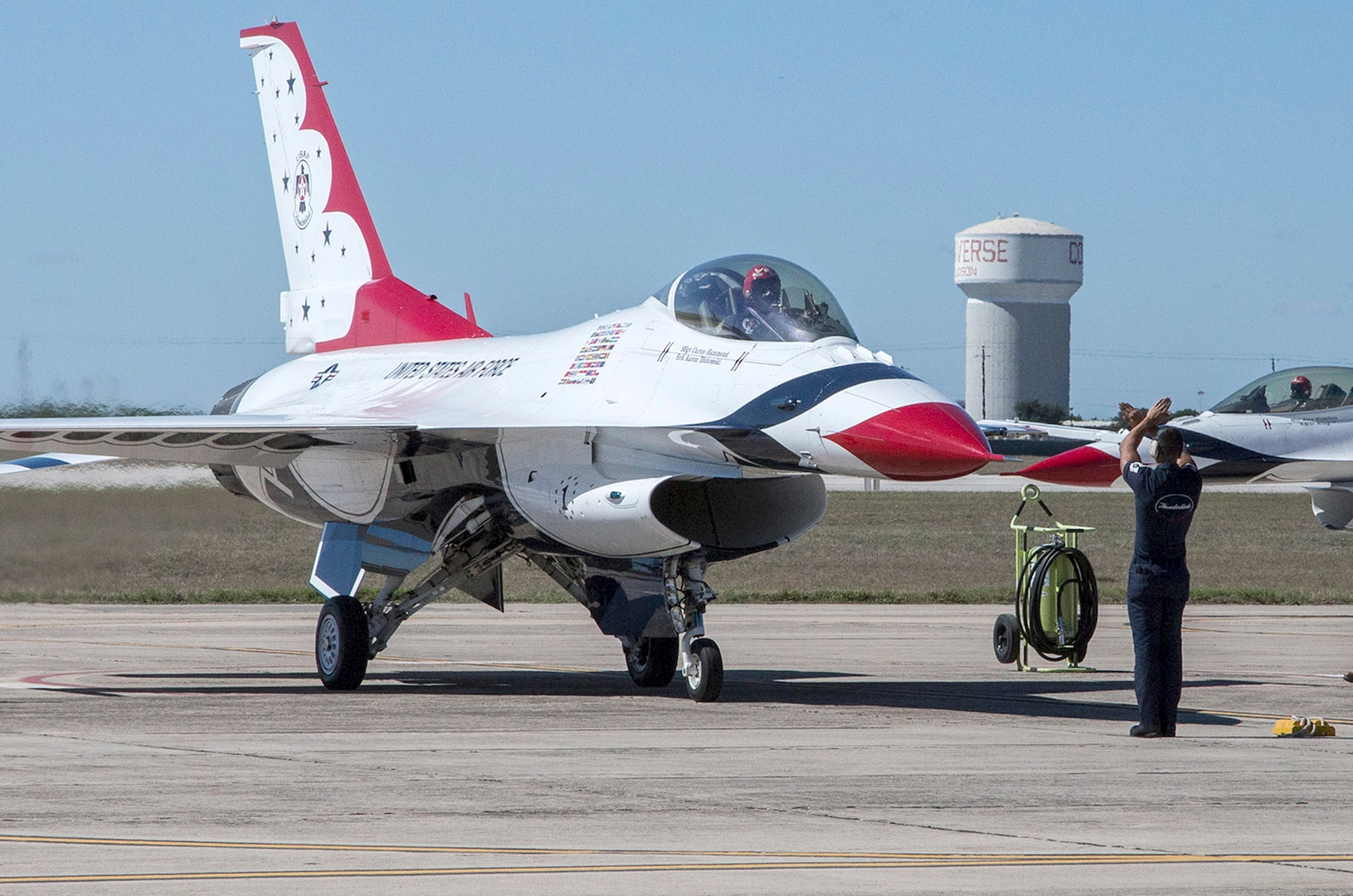 """Tech. Sgt. Christopher Audet, U.S. Air Force Air Demonstration Squadron """"Thunderbirds"""" tactical aircraft maintainer, guides a Thunderbird Oct. 26, 2015 at Joint Base San Antonio-Randolph, Texas. The Thunderbirds team members arrived in preparation for the 2015 JBSA-Randolph Air Show and Open House to be held Oct. 31 and Nov. 1.  Air shows allow the Air Force to display the capabilities of our aircraft to the American taxpayer through aerial demonstrations and static displays and allowing attendees to get up close and personal to see some of the equipment and aircraft used by the U.S. military today.  (U.S. Air Force photo by Johnny Saldivar/Released)"""