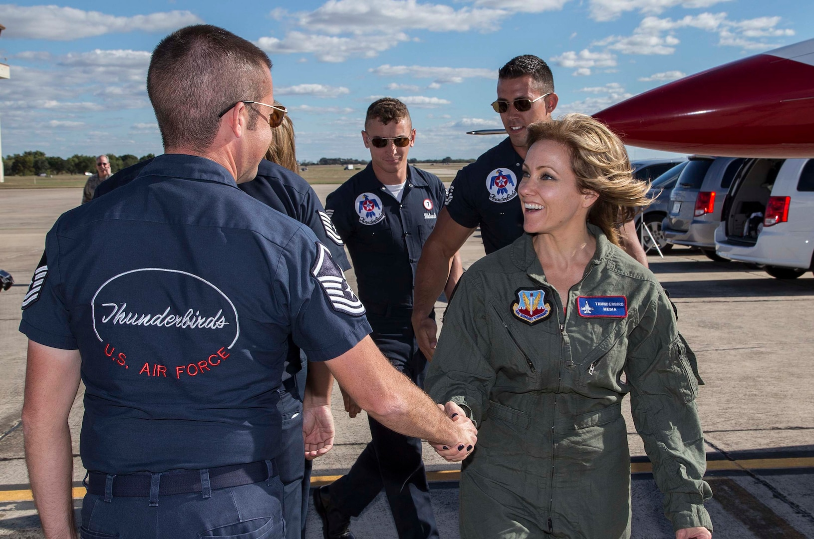 """Delaine Mathieu, News 4 San Antonio co-anchor, is greeted by U.S. Air Force Air Demonstration Squadron """"Thunderbirds"""" team members prior to a media flight Oct. 26, 2015 at Joint Base San Antonio-Randolph, Texas. The Thunderbirds are performing in the 2015 Air Show and Open House to be held at JBSA-Randolph Oct. 31 and Nov. 1. (U.S. Air Force photo by Johnny Saldivar/Released)"""