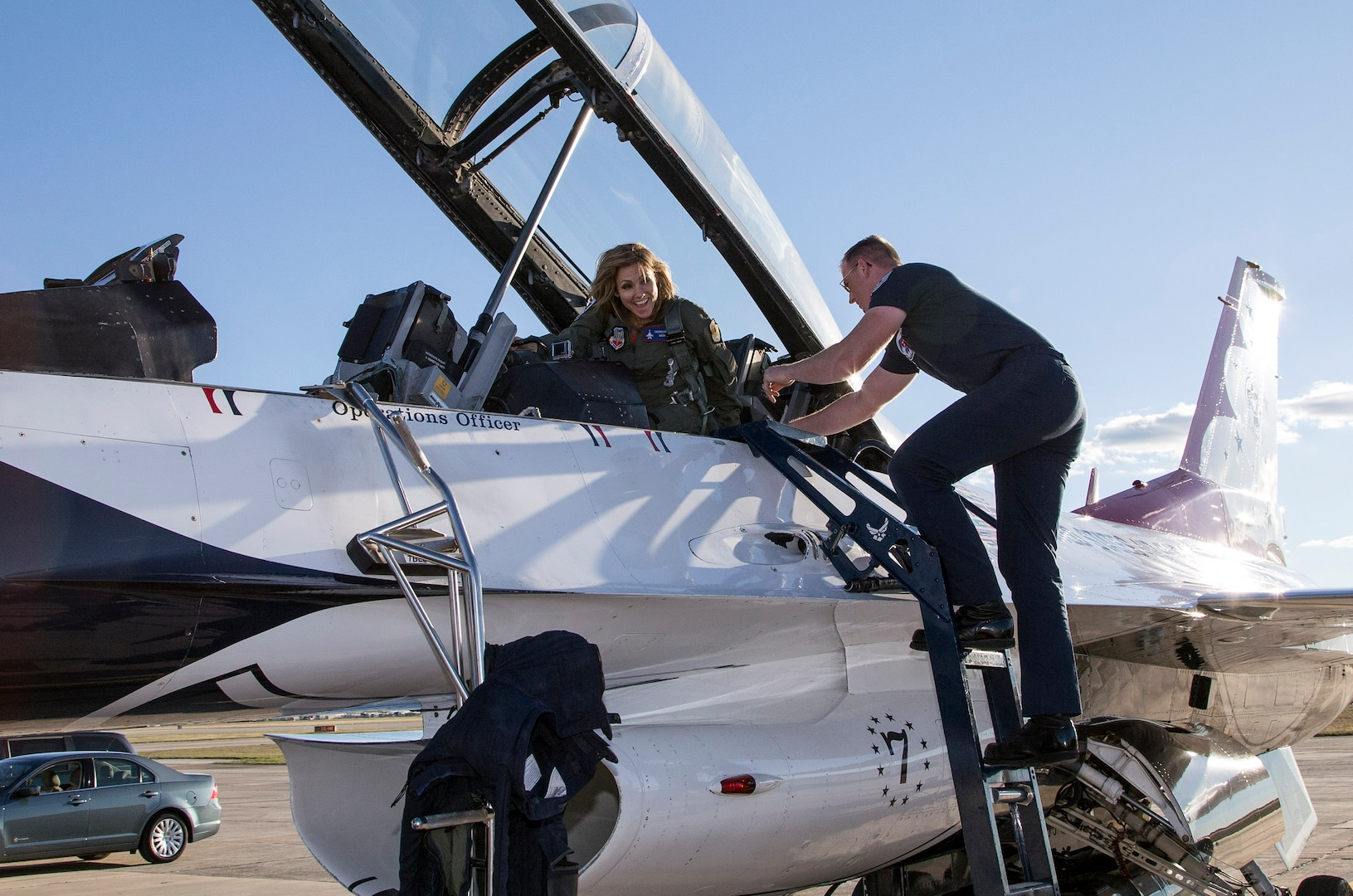 """Tech Sgt. Jacob Worthen, U.S. Air Force Air Demonstration Squadron """"Thunderbirds"""" avionics technician, assist Delaine Mathieu, News 4 San Antonio co-anchor, exit an F-16 aircraft Oct. 26, 2015 at Joint Base San Antonio-Randolph, Texas. The Thunderbirds are performing in the 2015 Air Show and Open House to be held at JBSA-Randolph Oct. 31 and Nov. 1. (U.S. Air Force photo by Johnny Saldivar/Released)"""
