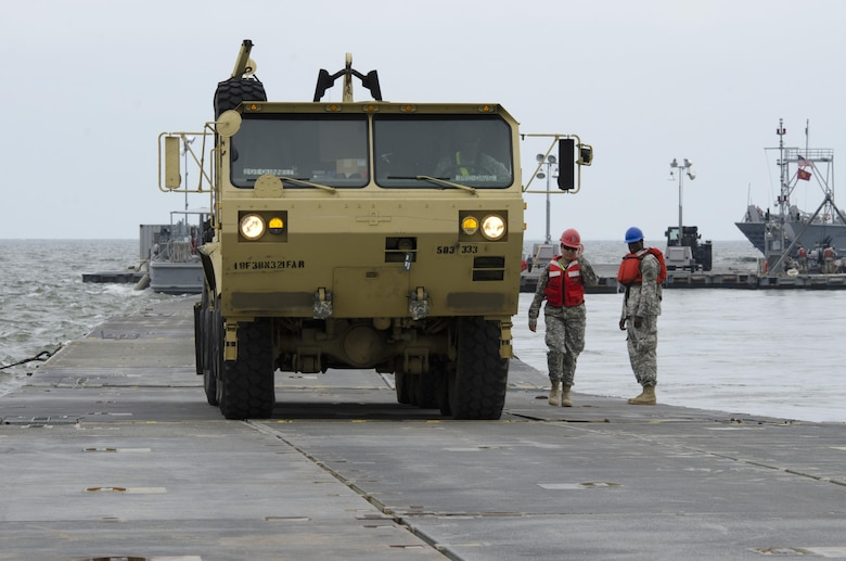 Cpl. Tauni Caldwell, 711th Transportation Company (Seaport Ops), acts as a walking guide for a heavy vehicle offloaded onto a floating causeway from a Landing Craft Mechanized watercraft (LCM) on Fort Story during Terminal Warrior 2015. The Logistics-Over-the-Shore (LOTS) exercise took place in the Hampton Roads area of Virginia from mid July through mid August and included Reserve, National Guard and Active Duty units focused on cohesion and sharpening proficiency in basic LOTS skills as part of the Total Army Concept