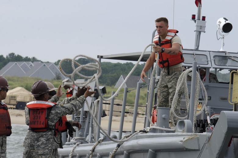 Pvt. 2 Seth Thorndell Rutter, 1098th Transportation Detachment (Medium Boat), throws a line from a Landing Craft Mechanized watercraft (LCM) to another Soldier to secure it for unloading operations at Fort Story during Terminal Warrior 2015. The Logistics-Over-the-Shore (LOTS) exercise took place in the Hampton Roads area of Virginia from mid July through mid August and included Reserve, National Guard and Active Duty units focused on cohesion and sharpening proficiency in basic LOTS skills as part of the Total Army Concept.