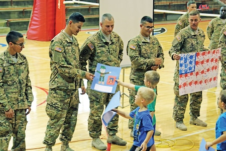 Spc. Ivan Barboza, a generator mechanic assigned to Company B, 299th Brigade Support Battalion, 2nd Armored Brigade Combat Team, 1st Infantry Division, receives a handmade gift from a student Sept. 10 during an assembly at Centre School in Lost Springs, Kansas.  Barboza, along with the other Soldiers in the company, ate lunch and attended classes with the students.  The partnership represents one of 22 the 2nd ABCT actively participates in as part of the Adopt-A-School Program and includes schools from Clay and Dickinson counties.