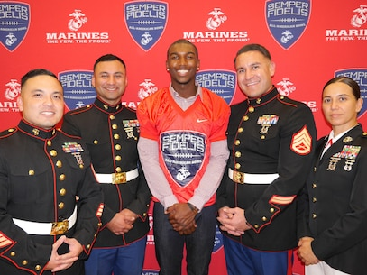 The Marines from Recruiting Sub Station Thousand Oaks and Recruiting Station Los Angeles Commanding Officer, Maj. Aixa Dones, right, pose for a photo with Theo Howard after he was presented with a jersey for the 2016 Semper Fidelis All-American Bowl at Westlake High School in Westlake Village, Oct. 8, 2015. (Courtesy photo)