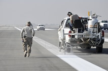 Airmen from the 455th Expeditionary Civil Engineer Squadron paint runway markings Oct. 22, 2015, at Bagram Airfield, Afghanistan. The paint is mixed with reflective beads to ensure that the markings can be seen by the pilots coming and going from Bagram in support of Operation Freedom's Sentinel and NATO's Resolute Support mission. (U.S. Air Force photo/Tech. Sgt. Nicholas Rau)