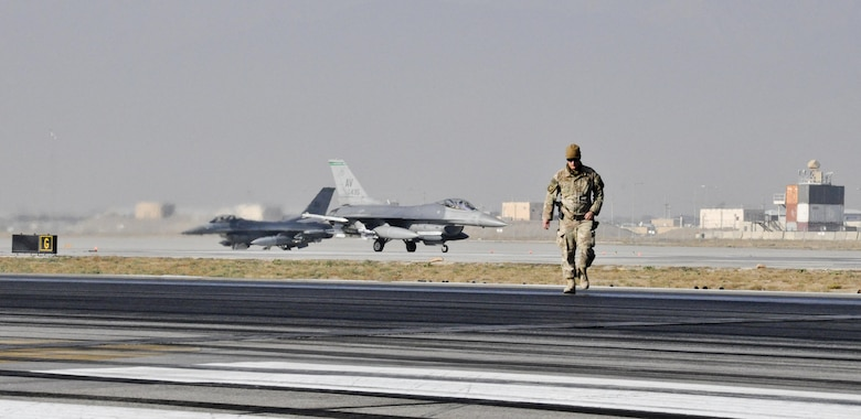Tech. Sgt. Christopher Fitzgerald, of the 577th Expeditionary Prime Base Engineer Emergency Force Squadron from Al Udeid Air Base, Qatar, inspects the runway as rubber is removed Oct. 22, 2015, at Bagram Airfield, Afghanistan. Foam and biodegradable solvents are used to strip the rubber left behind by the aircraft that land or take off from Bagram in support of Operation Freedom's Sentinel and NATO's Resolute Support mission. (U.S. Air Force photo/Tech. Sgt. Nicholas Rau)