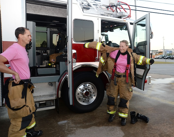 Firefighter/paramedic Ron Hedgecoke and emergency medical technician/firefighter Megan Cornell, both Fire Department personnel at Marine Corps Logistics Base Albany, suit up in response to a call during a simulated drill on the installation, recently. In keeping with the traditional October uniform-of-the-day, the duo wore pink T-shirts as a symbol of the department's efforts to heighten awareness and to show support in the fight against breast cancer.