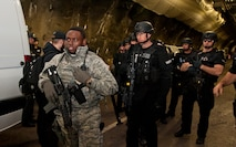 CHEYENNE MOUNTAIN AIR FORCE STATION, Colo. – Airman 1st Class Devin Hopkins, 721st Security Forces Squadron, leads El Paso County Sheriff's SWAT Team into Cheyenne Mountain Air Force Station's underground complex during an exercise, Oct. 22, 2015.  The SWAT Team was called to respond to an active shooter turned hostage exercise scenario in the systems center to negotiate with the simulated hostage taker and help with simulated victim evacuation. (U.S. Air Force photo by Senior Airman Tiffany DeNault))