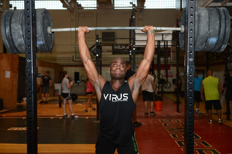 First Lt. Alex Johnson, 23rd Expeditionary Bomb Squadron electronic warfare officer, lifts weights during his functional fitness workout Oct. 21, 2015, at Andersen Air Force Base, Guam. The workout involves various exercises to include gymnastics, power lifting, cardio and Olympic weight lifting. (U.S. Air Force photo by Airman 1st Class Arielle Vasquez/Released)