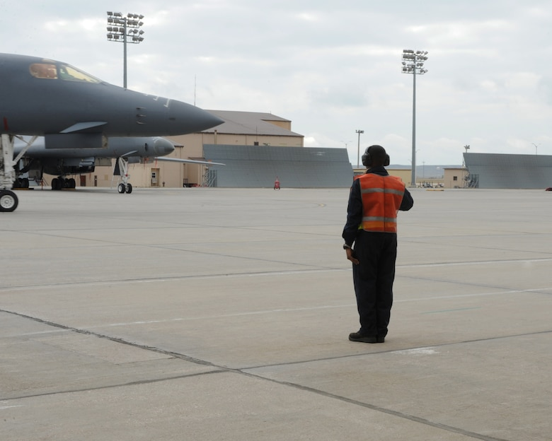 An Airman from the 28th Aircraft Maintenance Squadron marshals a B-1 bomber as part of surge week at Ellsworth Air Force Base, S.D., Oct. 5, 2015. During a surge,  the wing generates nearly double the amount of sorties typically flown each week. (U.S. Air Force photo by Airman 1st Class Denise M. Nevins/Released)