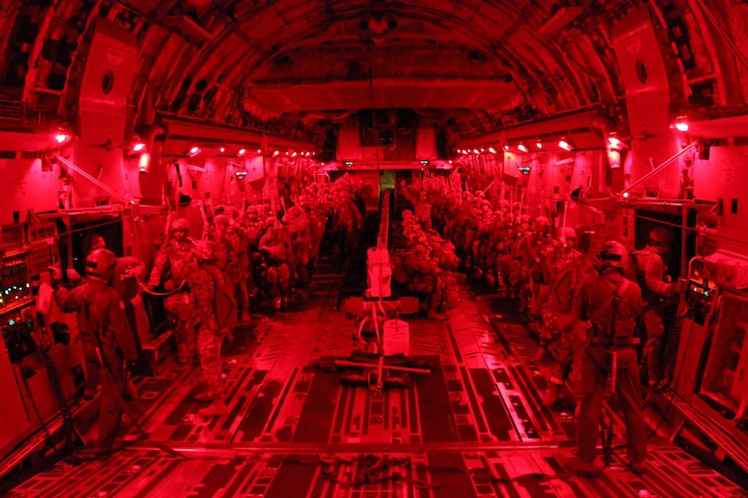 Army jump masters with the 3rd Squadron, 73rd Cavalry, 1st Brigade Combat Team, 82nd Airborne Division, conduct paratrooper door checks during a night tactical combat jump aboard a C-17 Globemaster III from the 437th Airlift Wing, while flying over Fort Bragg, North Carolina, Oct. 20, 2015. The purpose of the jump was to practice exiting the aircraft with cavalrymen and a full combat equipment load to secure a drop zone. The interior lights are red to remain tactical and assist the paratroopers adjust their eyes upon exiting the aircraft. (U.S. Army photo/Sgt. Chad Haling)