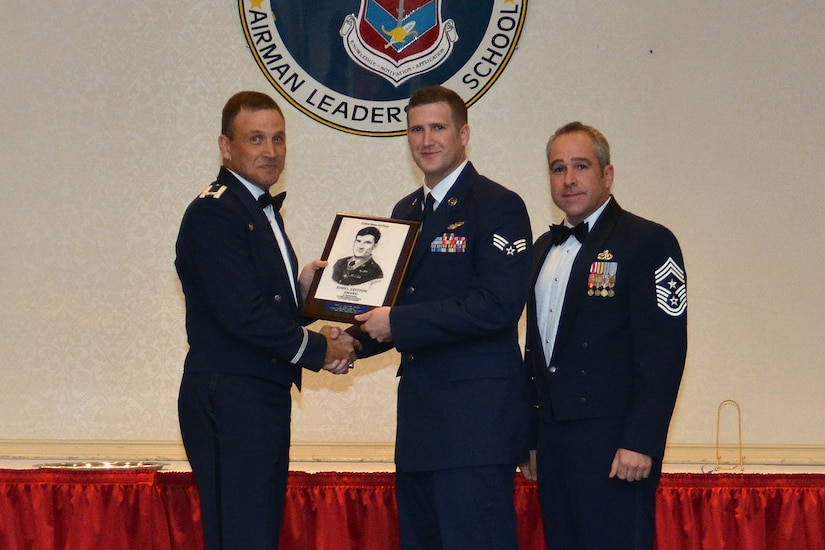 Col. Johnny Lamontagne, 437th Airlift Wing commander and Chief Master Sgt. Kristopher Berg, 437th AW command chief, present the John L. Levitow Award to Senior Airman Brian Loomis, 16th Airlift Squadron loadmaster, during the Airman Leadership School Class graduation October 22, 2015, at Joint Base Charleston - Air Base, S.C. The Levitow award is given for a student's exemplary demonstration of excellence, both as a leader and a scholar. (courtesy photo)