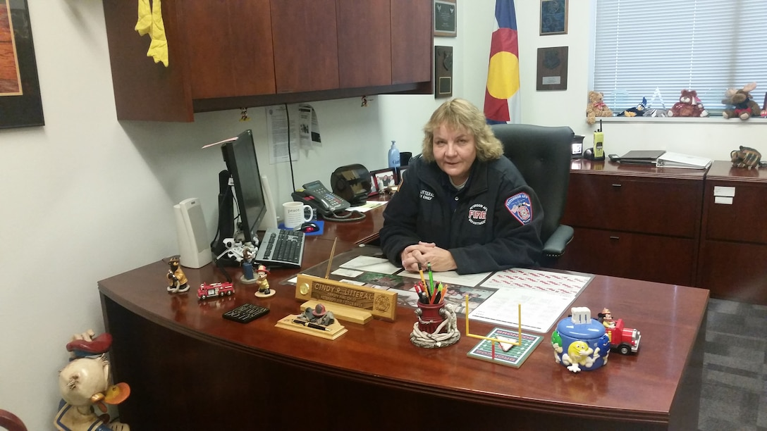 PETERSON AIR FORCE BASE, Colo. – Cindy Litteral, 21st Civil Engineer Squadron deputy fire chief, poses for a photo behind her desk Oct. 21, 2015. Litteral is scheduled to retire Oct. 30 after more than 30 years of service. She is the first and only female fire officer to receive the Department of Defense Fire Officer of the Year award. (U.S. Air Force photo by Lori O'Donley)