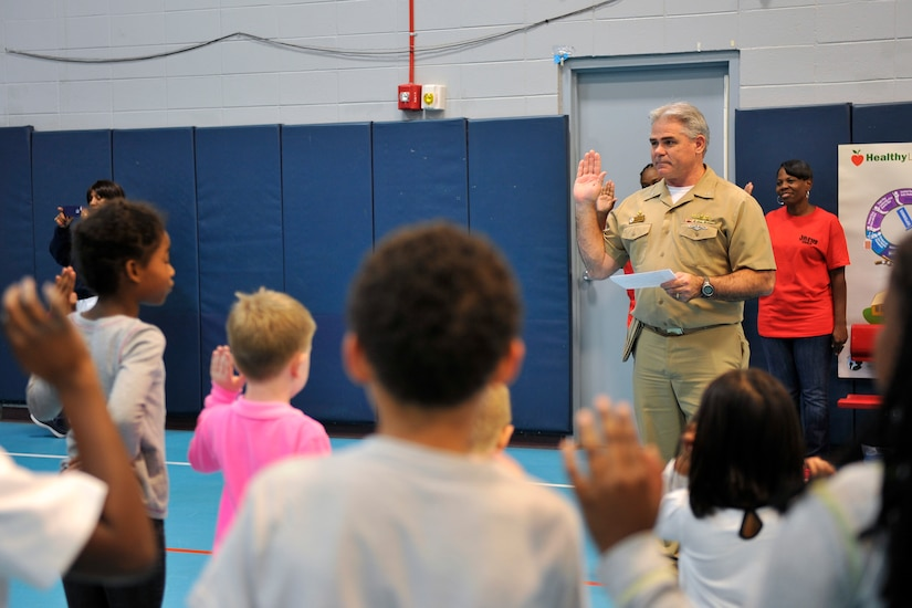 U.S. Navy Capt. Timothy Sparks, 628th Air Base Wing vice commander, administers an oath to children at the youth center at Joint Base Charleston, S.C., Oct. 23, 2015. The oath was a promise to be drug free, and was commemorated with a hand print and signature. (U.S. Air Force photo/Tech. Sgt. Renae Pittman)