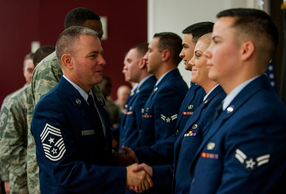 U.S. Air Force Chief Master Sgt. Brian Gates, 52nd Fighter Wing command chief, left, congratulates one of the new ceremonial guardsmen after the base Honor Guard training graduation ceremony inside the base theater at Spangdahlem Air Base, Germany, Oct. 23, 2015. As Spangdahlem's newest Honor Guardsmen, the graduates will travel in the largest area of responsibility in United States Air Forces in Europe, representing Spangdahlem and the USAF in all formal ceremonies requiring their service. (U.S. Air Force photo by Airman 1st Class Timothy Kim/Released)