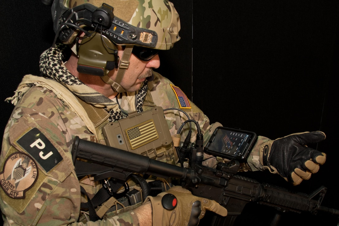 Chief Master Sgt. Robert Bean, an Air Force pararescue jumper, demonstrates how BATDOK can be worn on the wrist, providing awareness of the health status of multiple patients. Developing BATDOK required Air Force medical researchers to embed with pararescue jumpers on live missions to ensure the tool met the rigorous standards required by combat Airmen.