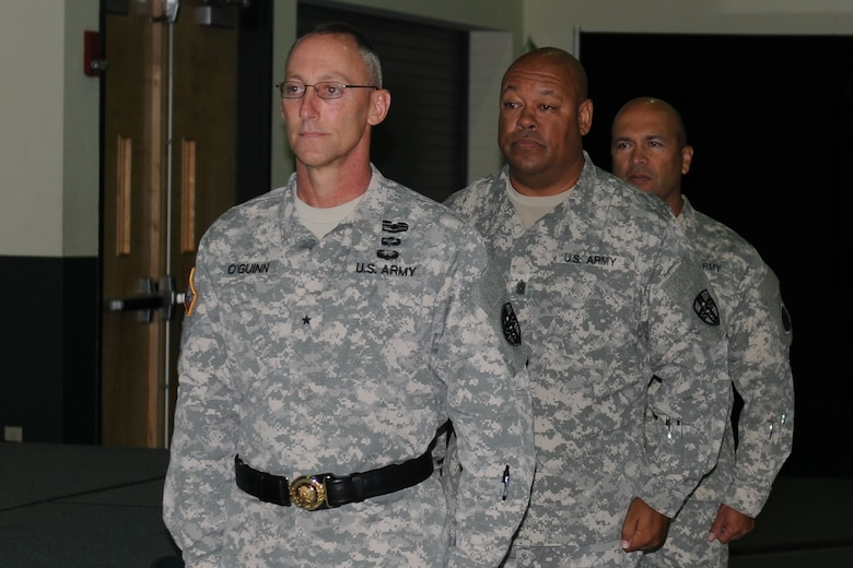 (Forefront) Brig. Gen. Michael C. O'Guinn Command, commanding general of the Medical Readiness and Training Command, (middle) Command Sgt. Maj. Marlo V. Cross, outgoing command sergeant major, and Command Sgt. Maj. Juan M. Loera Jr, incoming command sergeant major, stand ready to begin the change of responsibility ceremony, held at the Army Reserve Medical Command headquarters building in Pinellas Park, Fla., Sept. 24, 2015. Seattle resident Loera's previous assignment was command sergeant major for the 104th Training Division (Leader Training), Joint Base Lewis-McChord and Cross, a Tempe, Ariz., native, assumes responsibility of ARMEDCOM Sept. 26, 2015. The MRTC is based out of San Antonio.