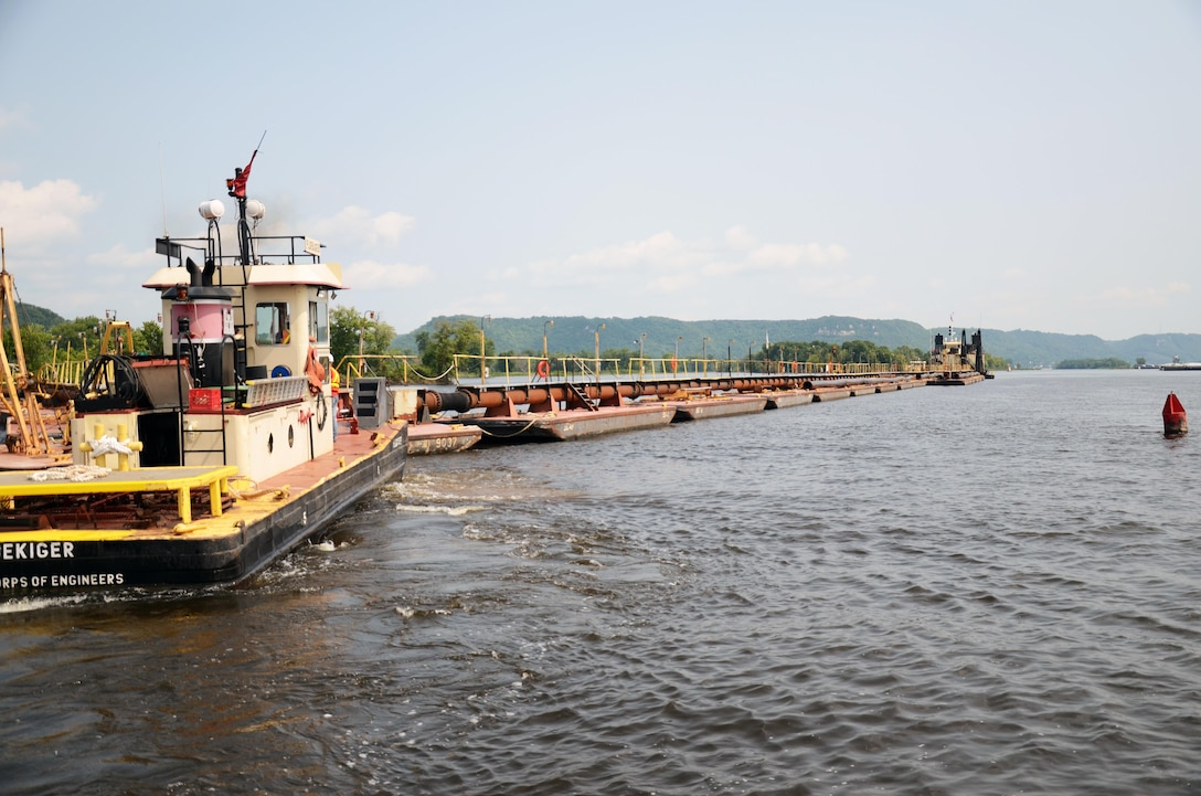 The Dredge Goetz, background, performs emergency dredging in Pool 4 of the Upper Mississippi River during the river's closure in July and August 2014.