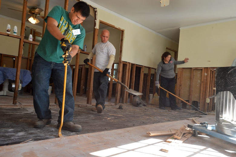 Two 20th Civil Engineer Squadron Airmen (left) and a disaster relief volunteer tear up wood floors at a home affected by the flooding in Sumter, S.C., Oct. 19, 2015. Organizations on Shaw Air Force Base, S.C., created multiple groups of more than 85 volunteers to assist in the disaster relief efforts for the Sumter community. (U.S. Air Force photo/Senior Airman Diana M. Cossaboom)