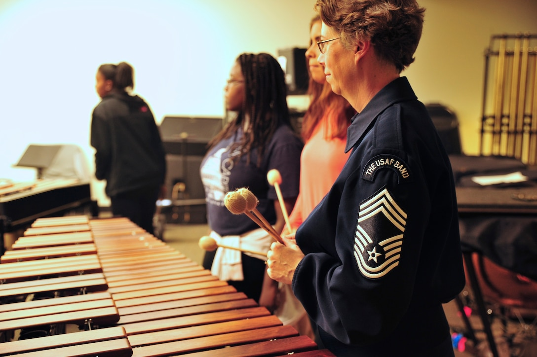 Chief Master Sgt. Erica Montgomery works with students during a clinic at Everett High School in Everett, Massachusetts while on tour with the Concert Band and Singing Sergeants for their Fall 2015 tour. The clinic was part of the Band's AIM program: Advancing Innovation through Music. (U.S. Air Force photo/released)