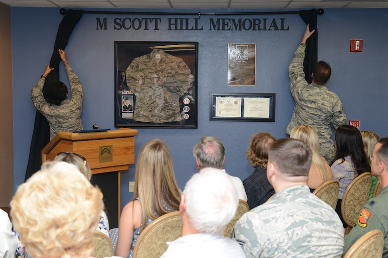 Staff Sgt. Alexena Simien, 56th Operations Support Squadron air traffic controller, and Senior Airman Samuel Bricker, 56th OSS air traffic controller, unveil Senior Airman Scott Hill's memorial wall during a dedication ceremony at Luke Air Force Base, Arizona, Oct. 26, 2015. Hill lost his battle with cancer and passed away May 18, 2014. The ceremony also retired Hill's air traffic controller initials: HI. The initials are a special identifier for controllers and HI will be Hill's at Luke forever. (U.S. Air Force photo by Senior Airman James Hensley)