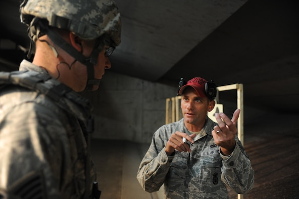 Staff Sgt. Nathan Warren, 28th Security Forces Squadron combat arms instructor, reviews proper firing techniques with Master Sgt. Peter Holtz, 28th SFS flight chief, at Ellsworth Air Force Base, S.D., Oct. 13, 2015. Prior to practical application on the range, students learn about firing stances, troubleshooting malfunctions and weapon maintenance. (U.S. Air Force photo by Airman Sadie Colbert/Released)