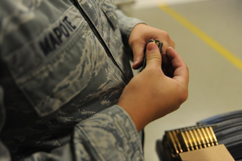Senior Airman BobbyLee Mapote, 28th Security Forces Squadron response force leader, loads an M9 pistol round into a magazine prior to weapons training at Ellsworth Air Force Base, S.D., Oct. 13, 2015. Ellsworth's combat arms training includes instruction on different types of ammunitions and how to load magazines. (U.S. Air Force photo by Airman Sadie Colbert/Released)