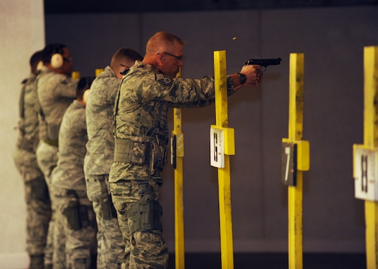 Airmen from the 28th Security Forces Squadron fire the M9 pistol during training at Ellsworth Air Force Base, S.D., Oct. 13, 2015. Prior to firing, personnel receive instruction on safety and weapon control using multiple weapon systems. (U.S. Air Force photo by Airman Sadie Colbert/Released)