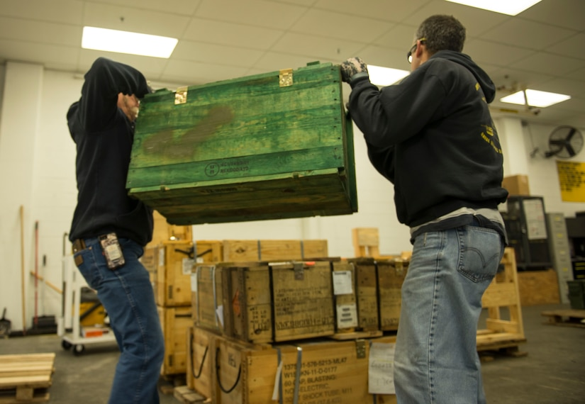 (From left to right) Naval Munitions Command Atlantic Unit Charleston work leaders, Bryan Shaw and Mark Lamoureux, stack a crate of equipment to complete a pallet on Oct. 27, 2015, at Joint Base Charleston – Naval Weapons Station. The pallet is one of several that will be included in a much larger storage container to be loaded on the United States Naval Ship Red Cloud.