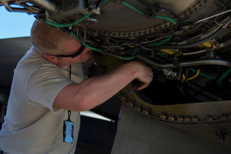 BEJA AIR BASE, Portugal – U.S. Air Force Staff Sgt. Christopher Lancaster, 52nd Component Maintenance Squadron aerospace propulsion technician, works on the engine of an F-16 Fighting Falcon fighter aircraft, assigned to the 480th Fighter Squadron at Spangdahlem Air Base, Germany, before it participates in Trident Juncture 2015 at Beja Air Base, Portugal, Oct. 22, 2015. NATO exercises such as Trident Juncture provide an excellent venue for current and hopeful NATO members to work on their warfighting, communication and coordination skills. (U.S. Air Force photo illustration by Airman 1st Class Luke Kitterman/Released)