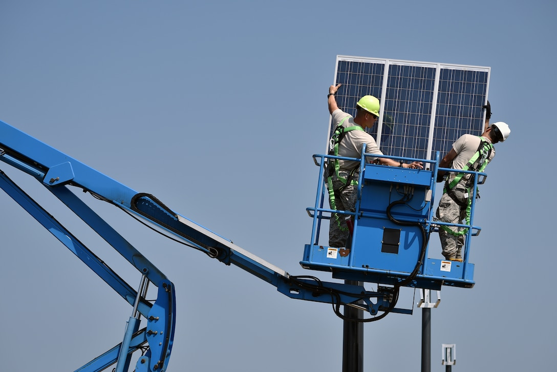 WESTHAMPTON BEACH, NY - Staff Sgt. Edwin Laporte and Hector Gomez, both members of the 106th Civil Engineering Squadron, 106th Rescue Wing install a solar panel at FS Gabreski ANG on September 8, 2015.