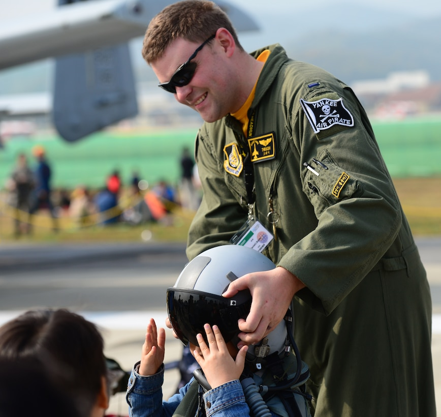 First Lt. Daniel Brom, of the 80th Fighter Squadron, Kunsan Air Base, South Korea, helps a local Korean boy try on a flight helmet at the 2015 Seoul International Aerospace and Defense Exhibition held at Seoul Airport, South Korea, Oct. 24, 2015. The Seoul ADEX gives American service members a chance to interact with the Korean public while showcasing their outstanding aircraft and equipment. (U.S. Air Force photo/Staff Sgt. Amber Grimm)