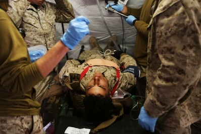 Navy Corpsmen and medical officers with Combat Logistics Battalion 11, 1st Marine Logistics Group, treat a Marine with a sucking chest wound after a simulated suicide bomber attack during Mountain Exercise 6-15 at Marine Corps Mountain Warfare Training Center, Bridgeport, Calif., Oct. 25, 2015. Engineer Platoon conducted two consecutive days of security patrols to ensure the safety of the base camp and was confronted with the challenge of a mass casualty event at the end of their patrol.