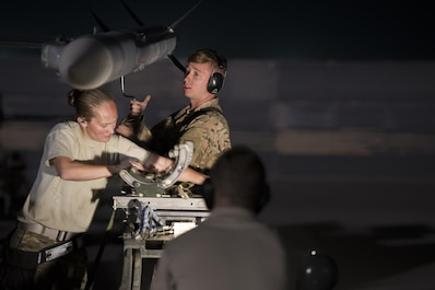 Staff. Sgt. Jeanette Martinez, 455th Expeditionary Aircraft Maintenance Squadron weapons team chief, and Senior Airman Christopher Wessig, 455th EAMXS deployed from Hill Air Force Base, Utah, load a missile onto an F-16 Fighting Falcon at Bagram Airfield, Afghanistan, Oct. 28, 2015. The 421st Fighter Squadron from Hill AFB will relieve the 555th Expeditionary Fighter Squadron from Aviano Air Base, Italy this month. (U.S. Air Force photo by Tech. Sgt. Robert Cloys/Released)
