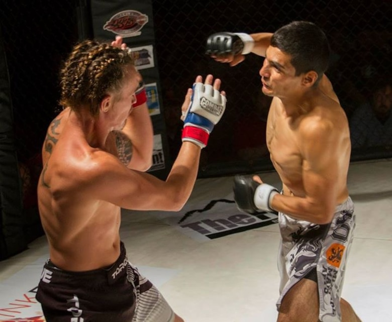 Senior Airman Mark Wirth, a 819th RED HORSE Squadron structural engineer (right), battles his opponent in the mixed martial arts octagon Aug. 23, 2015, in Great Falls, Mont. Wirth currently holds an 8-0 fight record. (Courtesy photo)